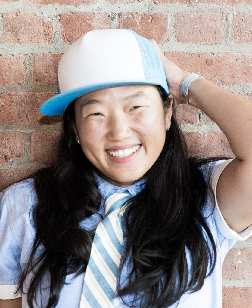 Photo of Arhm Choi Wild by Katharine Reece. Author with long, black hair, smiling broadly at the camera and wearing a baby blue-and-white baseball cap, a pale blue, short-sleeved,  buttoned shirt, rolled up at the sleeves, a watch with a white band, and a cream tie that has blue and taupe diagonal stripes. The subject's left arm is raised and her hand placed behind her head in a jaunty, carefree fashion.