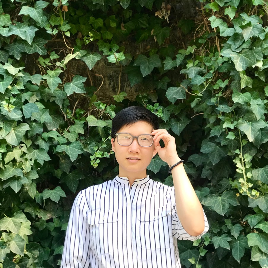 Photo of Karen Zheng by Ray Ren (Poet with short hair and brown-rimmed glasses, wearing a black-and-white striped buttoned shirt and standing in front of a background of ivy)