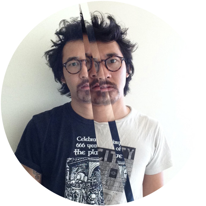 Photo of Thad Higa, artist with thick-rimmed, dark glasses, a goatee, and dark, slightly wavy hair that is styled to jut away from his head at angles and frame his face. In this portrait, composited from two photos spliced together in four angular strips, he wears two different t-shirts (one black and one white) and stares intently at the camera.