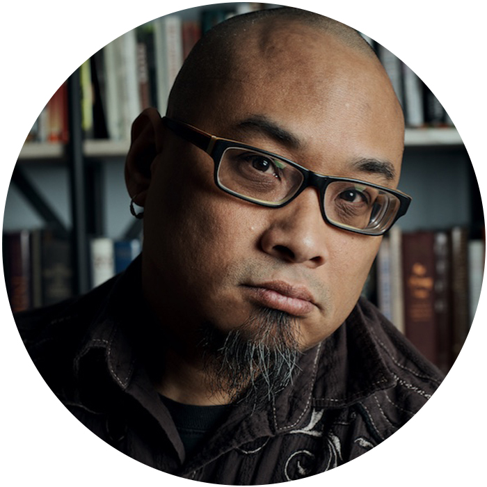 Photo of W. Todd Kaneko  (Portrait of the poet, wearing black, rectangular glasses, a brown collared shirt with white embroidery on the yoke buttoned over a black tee, and a goatee. Books on white shelves line the wall in the background).